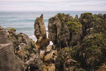 From above of rocky overgrown of plants seashore with waves and cloudy sky in pancake rocks in New Zealand Fotobehang