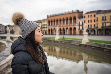 Foto op Plexiglas Historisch mon. Side view of young Asian resting lady in warm clothing and hat walking at beautiful Prato della Valle park at Padova at Italy