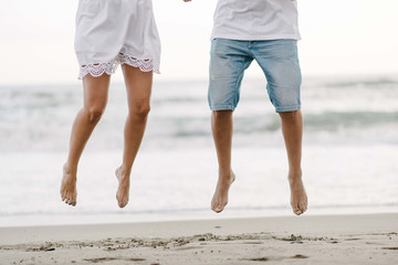 Crop barefoot legs of happiness couple on vacation in summer wear jumping on sandy empty seashore