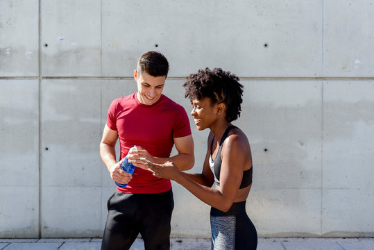 Cheerful man with bottle of water and African American woman sharing smartphone standing together against concrete wall and using app for training while having break in city