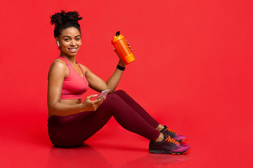 Sporty young woman listening to music, drinking water