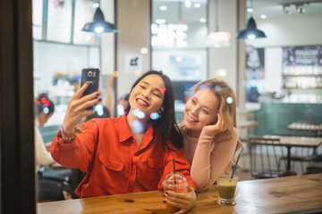 Two young woman friends with cups of fresh coffee smiling and posing for selfie while sitting at table in cozy restaurant having a beverage
