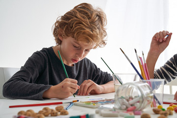 Little boy with curly hair smiling while sitting at table and painting against white wall at home