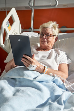 Cheerful elderly woman using tablet on hospital bed