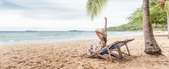 Happy woman vacation on the beach chair under palm tree. Fotomurales
