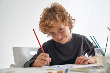 Little boy with curly hair smiling and looking at camera while sitting at table and painting against white wall at home
