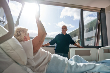 Senior male visitor standing near window and speaking with female patient in ward of modern hospital