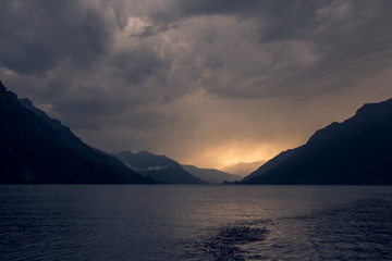 Calm landscape of dark rippled water under gray cloudy sky in mountains in Switzerland Fotobehang