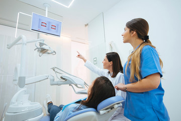 Dentist and assistant showing structure of teeth in picture to client in chair