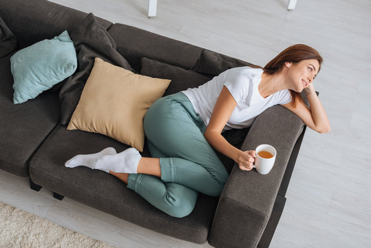 overhead view of attractive woman chilling of sofa with cup of tea
