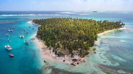 Aerial View of the San Blas Islands in Panama. Sailing Yachts & Sailboats anchoring next to Tropical Island with green Palm Trees and white sand Beaches surrounded by Coral Reefs in the Caribbean Sea.