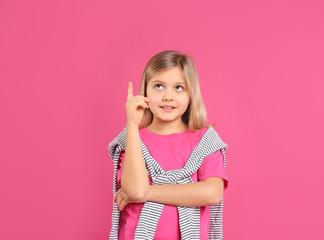 Cute little girl wearing casual outfit on pink background