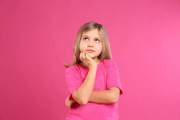 Thoughtful little girl wearing casual outfit on pink background