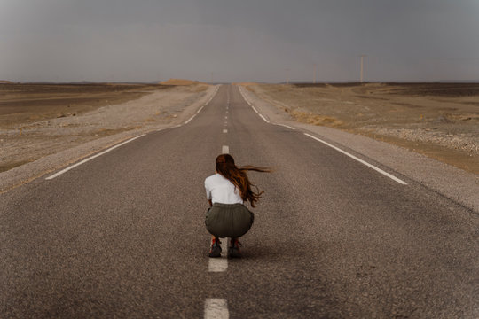Back view of woman crouching on median strip of empty country road, Fez, Morocco