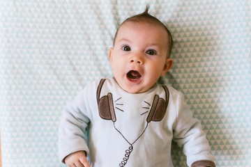 Portrait of surprised baby girl with appliqued headphones on pajamas