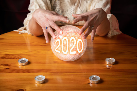 Fortune Teller with Crystal Ball on table with candles and year 2020 in ball