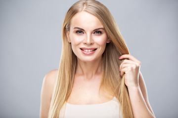 Beautiful blonde woman with shiny long straight hair and natural fresh make up. Fashion beauty portrait isolated