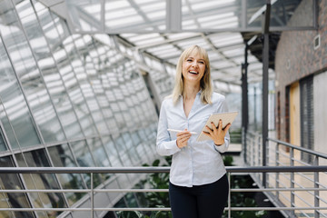Laughing young businesswoman in a modern office building using tablet