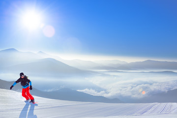 Snowboarder Riding Red Snowboard on the Slope in the Mountains in Bright Sun. Snowboarding and Winter Sports Concept