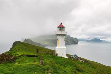 Foggy view of old lighthouse on the Mykines island, Faroe islands, Denmark. Landscape photography