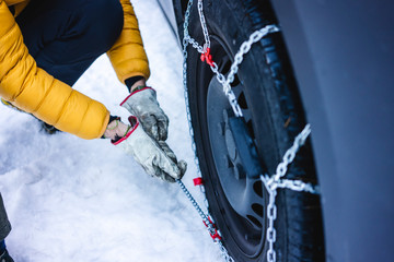 Man putting the snow chains on his car