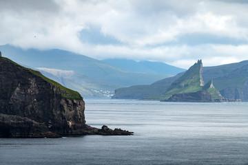 Dramatic view on Drangarnir and Tindholmur sea stacks in Atlantic ocean from Mykines island, Faroe Islands. Landscape photography