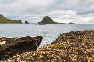 Dramatic view on Drangarnir and Tindholmur sea stacks in Atlantic ocean from Vagar island, Faroe Islands. Landscape photography
