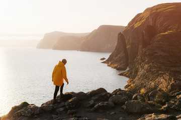 Tourist in yellow jacket looks at cliffs near Sorvagsvatn lake on Vagar island, Faroe Islands, Denmark. Landscape photography