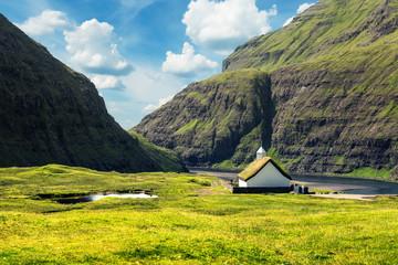Summer view of traditional turf-top church Saksunar Kirkja in Saksun village. Beauty landscape with Pollurin Laguna and high mountains. Streymoy island, Faroe Islands, Denmark.