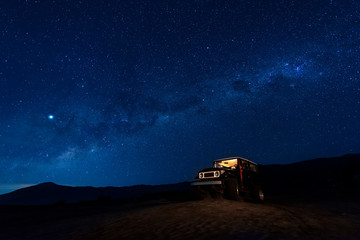 Indonesia, East Java, Milky Way galaxy on blue starry night sky over car parked in Bromo Tengger Semeru National Park