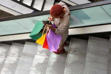 Young woman holding colorful shopping bags and checking her cell phone while descending the stairs