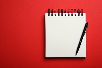 Stylish open notebook and pen on red background, top view. Space for text