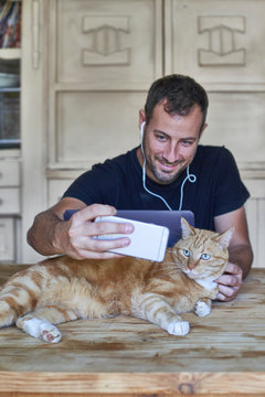 Man sitting at table, taking picture of his ginger cat with smartphone