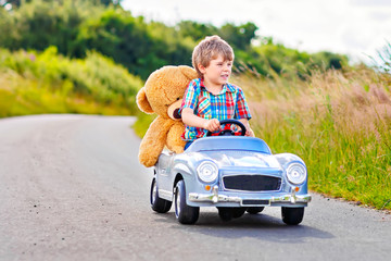 Little preschool kid boy driving big toy car and having fun with playing with his plush toy bear, outdoors. Child enjoying warm summer day in nature landscape.