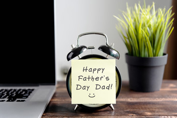 Happy Father's Day wish on sticky note on top of table