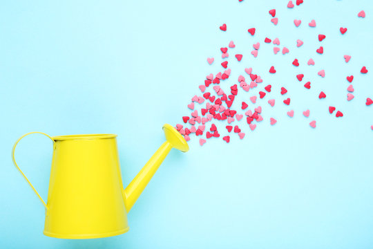 Heart shaped sprinkles with watering can on blue background