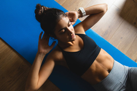 Fitness workout at home. Healthy fit young woman exercising.