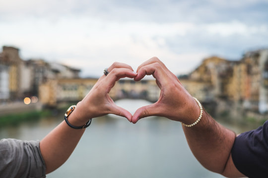 Young couple hands united in a heart shape. Florence Italy
