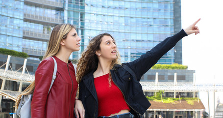 Two female friends walking ina modern city and talking