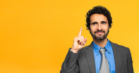 Young businessman having the solution on yellow background