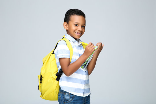Young African American school boy writing in notepad with backpack on grey background
