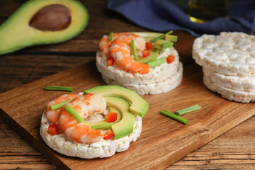 Puffed rice cakes with shrimps and avocado on wooden table