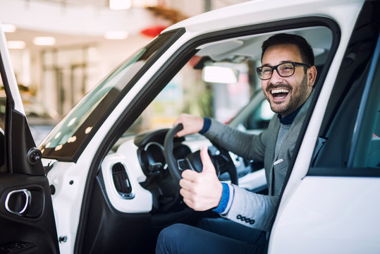 Happy satisfied customer just bought a brand new car at vehicle dealership. Car buyer sitting at drivers position and holding thumbs up.