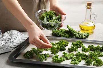 Woman preparing kale chips at table, closeup