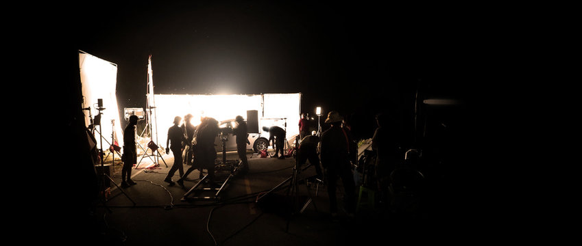 Silhouette images of video production behind the scene or b-roll or making of film shooting and movie crew team working in back of camera and lighting soft box equipment set at outdoor in the night