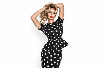 Beautiful fashion model, dressed in pinup style black dress in white polka dot, isolated over white background. Caucasian trendy blond girl.