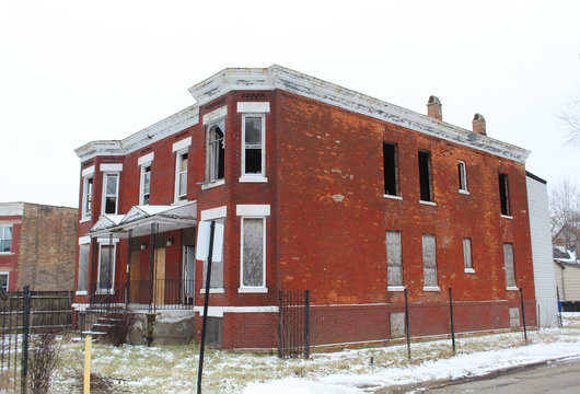 Abandoned small red brick apartment building in Chicago's Englewood neigbhorhood in winter