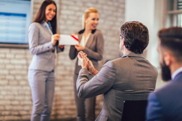 Front view of woman receiving award from businesswoman in front of business professionals applauding at business seminar in office building