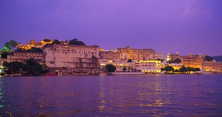 Wall Mural - Udaipur City Palace on bank of lake Pichola with tourist boat - Rajput architecture of Mewar dynasty rulers of Rajasthan. Sunset at Udaipur, India