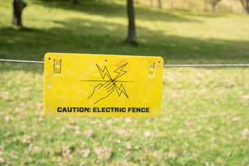 Bright Yellow Sign: Caution Electric Fence, Hanging on Fence in front of Grass